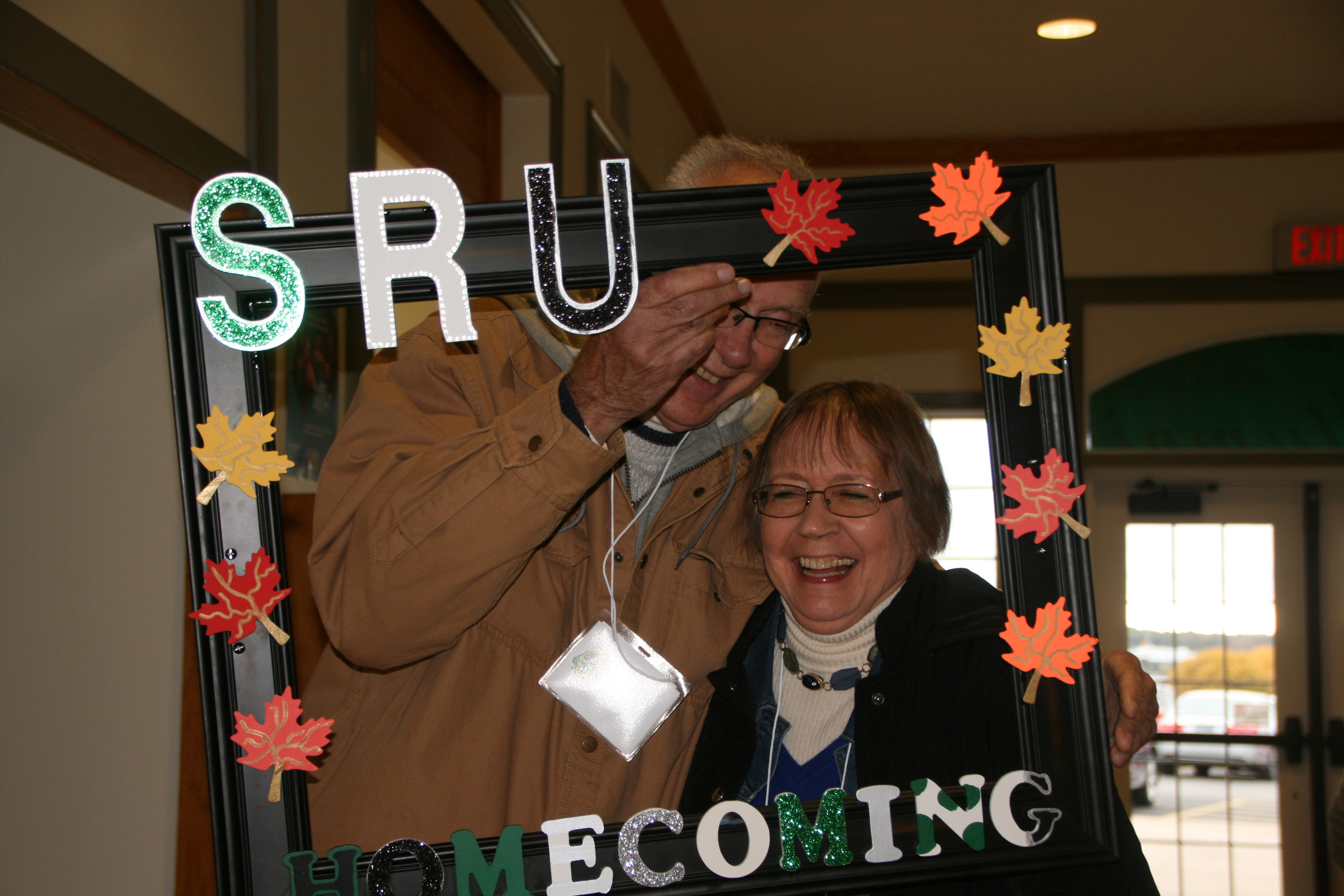 Married couple holding up SRU Homecoming frame